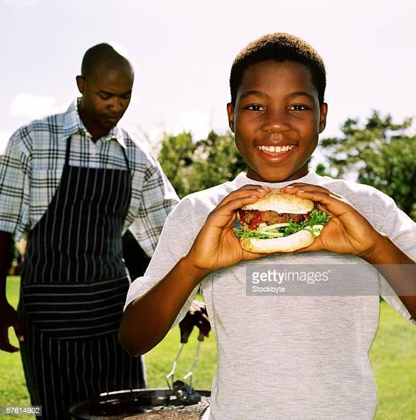 A young boy (12-13) eating a burger with his father barbecuing behind him