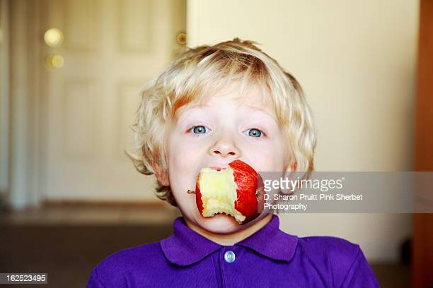 Young boy eating a red apple
