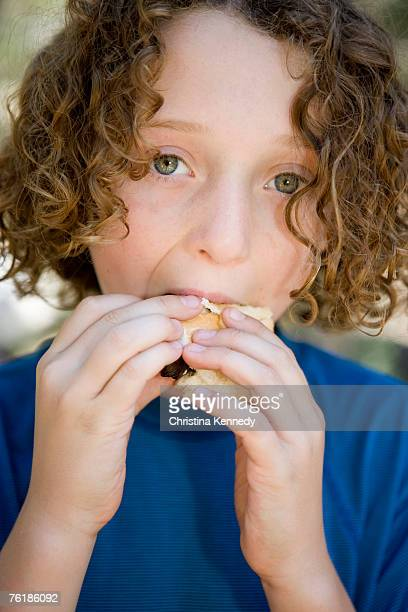 A young boy eating a sausage in a bread roll