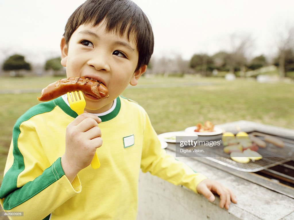 Young Boy Eating a Sausage : Stock Photo