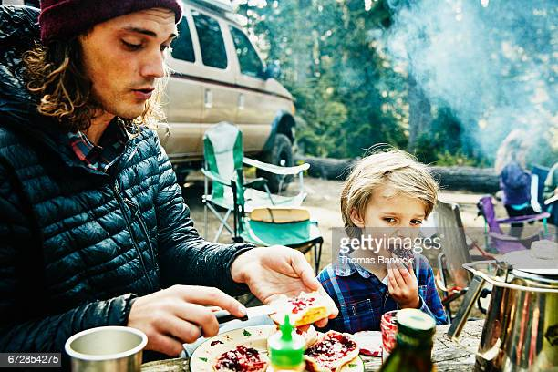Young boy eating biscuits with jam while camping