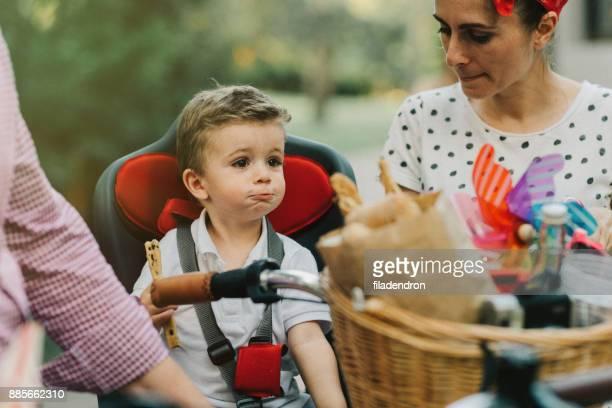 Kleiner Junge Grissini auf einem Fahrrad Essen