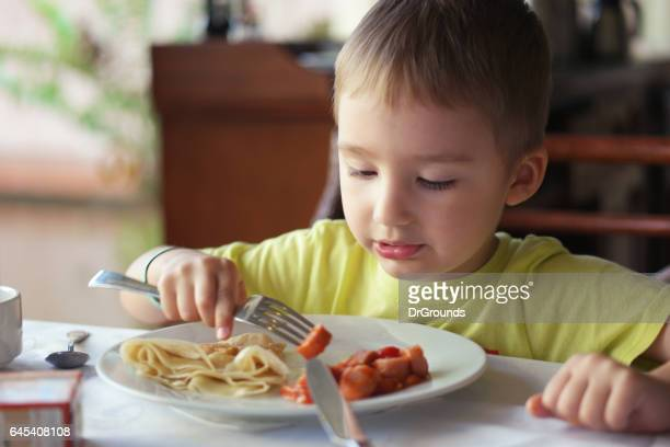 Young boy eating breakfast by himself