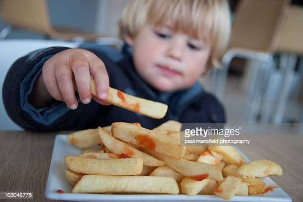 young boy eating chips - fast food french fries stock pictures, royalty-free photos & images
