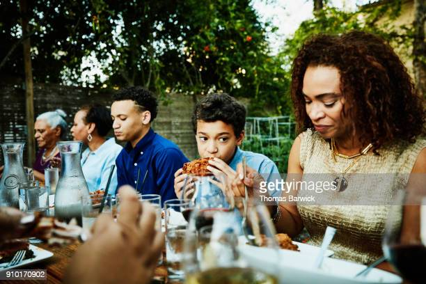 young boy eating fried chicken during outdoor family dinner party - fried chicken stock photos and pictures