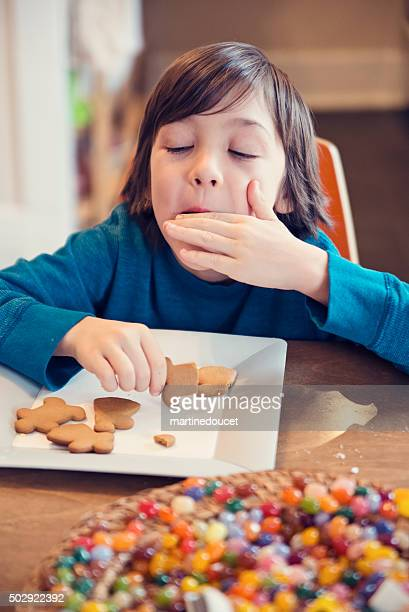 "young boy eating gingerbread cookies with expressive face. - ""martine doucet"" or martinedoucet bildbanksfoton och bilder"