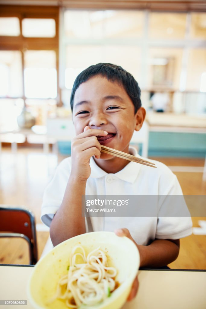 Young boy eating his school lunch at preschool : Stock Photo