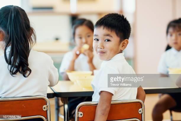 young boy eating his school lunch at preschool - 公共の建物 ストックフォトと画像