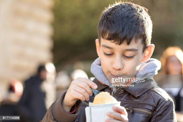 Young boy eating icecream outdoors