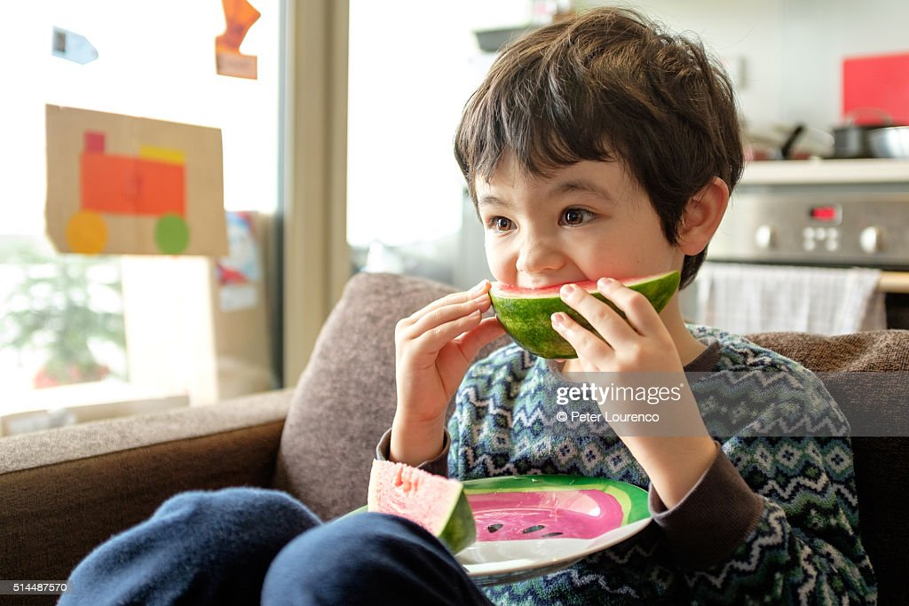 Young boy eating water melon : Stock Photo