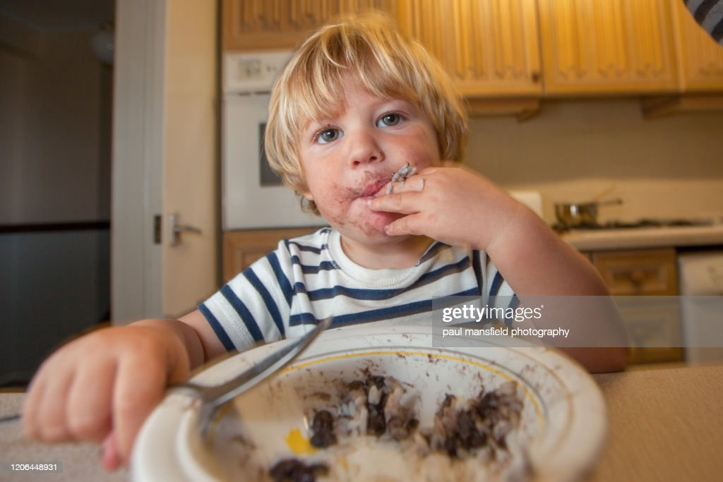 Young boy eating with a spoon : Stock Photo