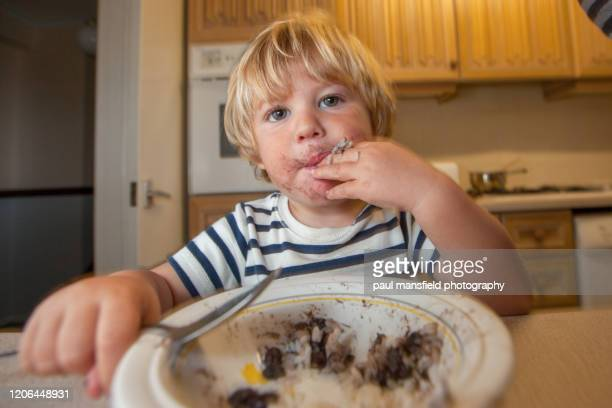 young boy eating with a spoon - eating stock pictures, royalty-free photos & images