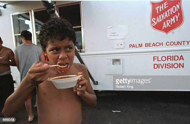 A young boy eats a bowl of hot soup October 5 2000 at a mobile Salvation Army disaster relief kitchen in Miami Heavy rains from a tropical depression...