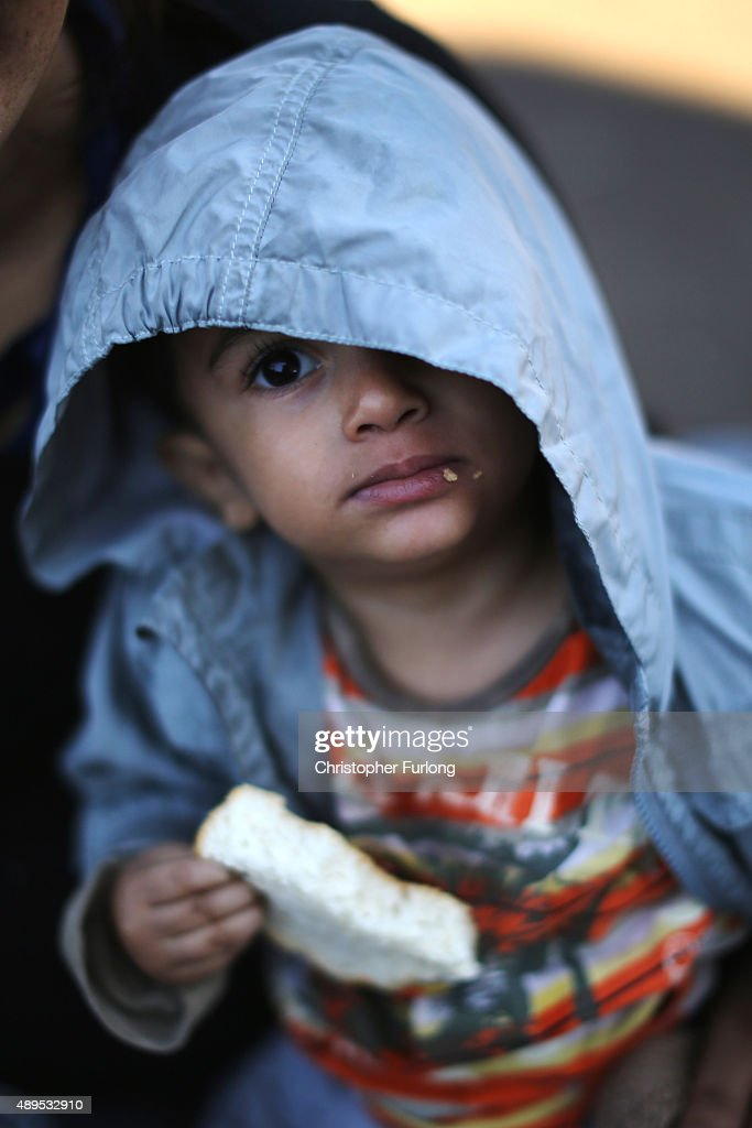 A young boy eats bread given out by the Hungrian Red Cross, as hundreds of migrants who arrived by train at Hegyeshalom on the Hungarian and Austrian border, walk the four kilometres into Austria on September 22, 2015 in Hegyeshalom, Hungary. Thousands of migrants have arrived in Austria over the weekend with more en-route from Hungary, Croatia and Slovenia. Politicians across the European Union are holding meetings on the refugee crisis with EU leaders attending an extraordinary summit on Wednesday to try and solve the crisis and the dispute of how to relocate 120,000 migrants aross EU states.