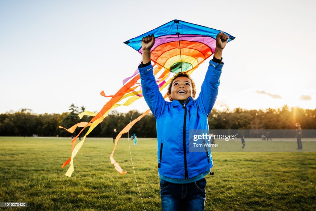 Young Boy Enjoying Learning How To Fly Kite : Stock Photo