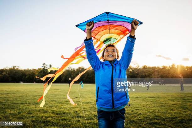 young boy enjoying learning how to fly kite - kindheit stock-fotos und bilder