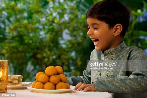 young boy enjoying - diwali sweets stock photos and pictures