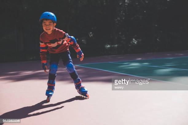 young boy enjoying roller skating - caneleira roupa desportiva de proteção imagens e fotografias de stock