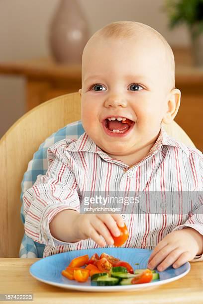 Jeune garçon dégustant un en-cas dans la chaise haute