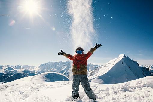 Young boy enjoying sun and snow fun on top of a mountain - gettyimageskorea