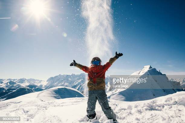 Young boy enjoying sun and snow fun on top of a mountain