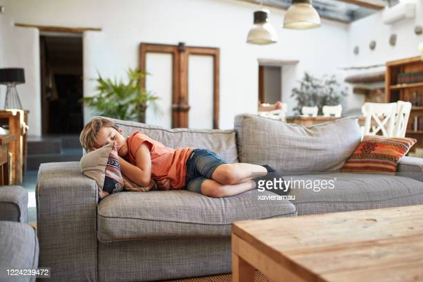 リビングルームソファで週末の昼寝を楽しむ若い男の子 - 昼寝 ストックフォトと画像