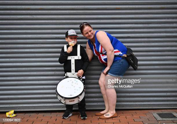 Young boy enjoys an ice-cream as he watches on with his mother as the annual Twelfth of July march takes place on July 12, 2021 in Belfast, Northern...