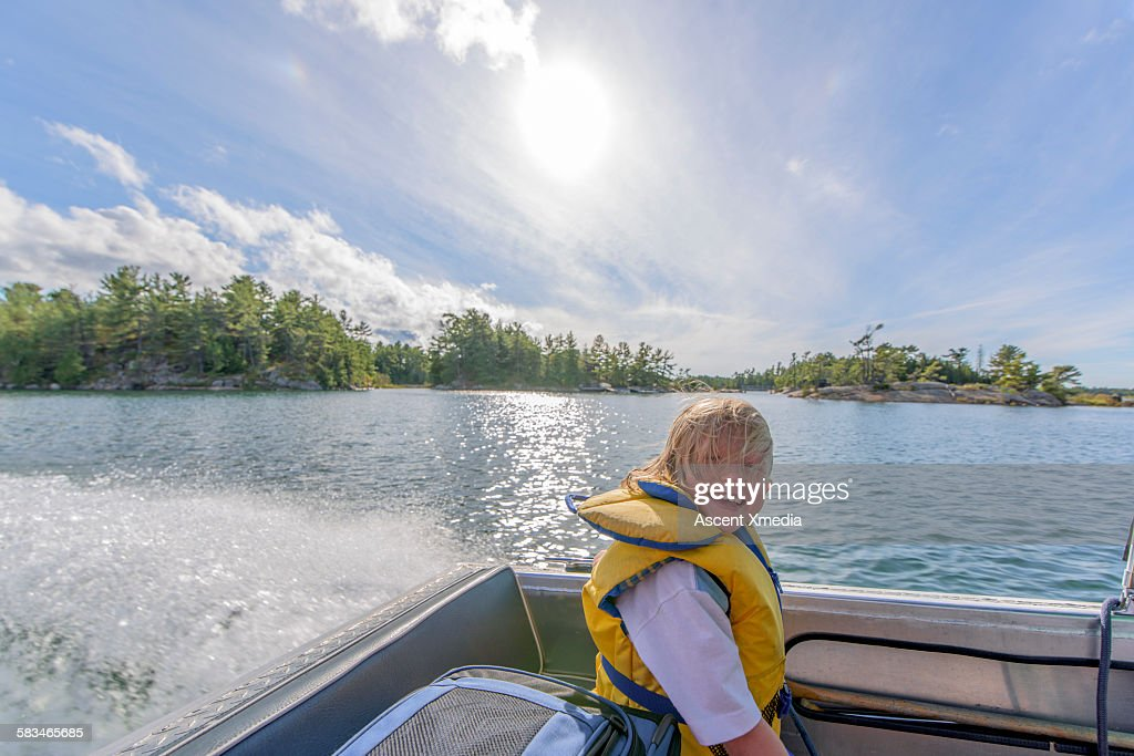 Young boy enjoys ride in stern of motorboat : Stock Photo