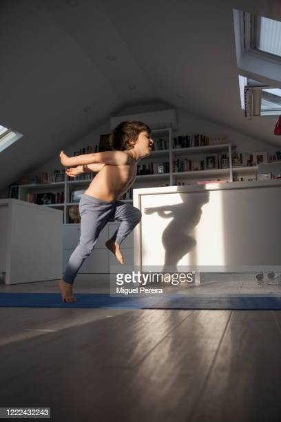 young boy exercising at home - alto posición descriptiva fotografías e imágenes de stock