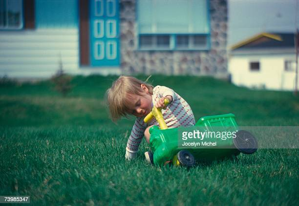 Young boy falling off a ride-on plastic toy