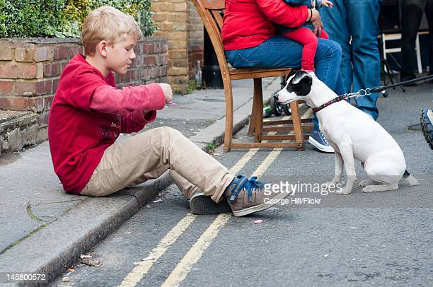 Young boy feeding a dog during the diamond jubilee celebrations. Shot was taken outside the Jolly woodman pub on Cambridge road in Beckenham, Kent. A...