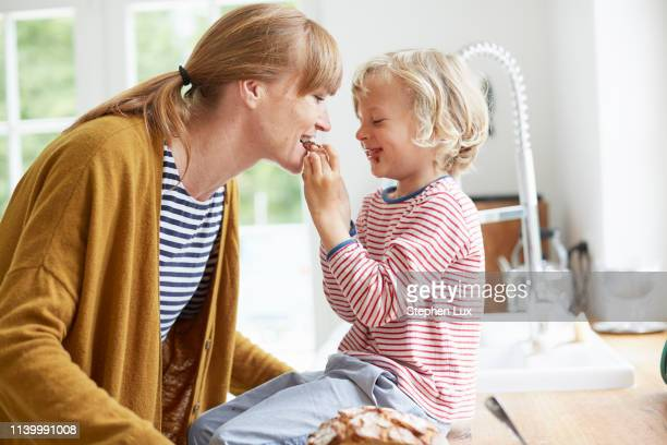 young boy feeding mother a sweet treat - nutella stock pictures, royalty-free photos & images