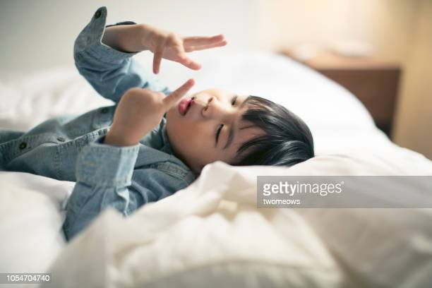 young boy finger counting in bed. - counting stock pictures, royalty-free photos & images