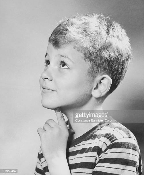 young boy finger touching chin looking up - number of people stock pictures, royalty-free photos & images