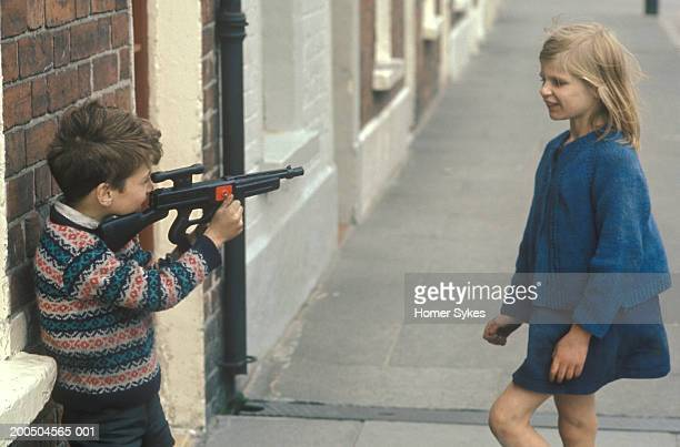 A young boy fires a pretend toy rifle gun at a young girl in the street The Troubles