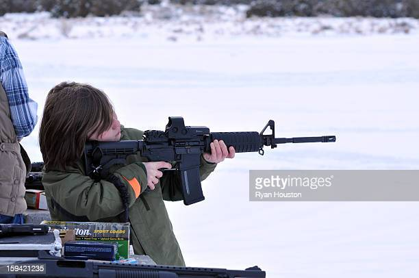 Young boy fires an AR-15 assault rifle at a shooting range. He was enjoying target practice. The gun has a high capacity round magazine such as the...