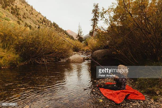 Young boy fish beside creek, Mineral King, Sequoia National Park, California, USA