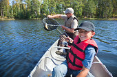 Young boy fisherman smiles at catch of nice walleye
