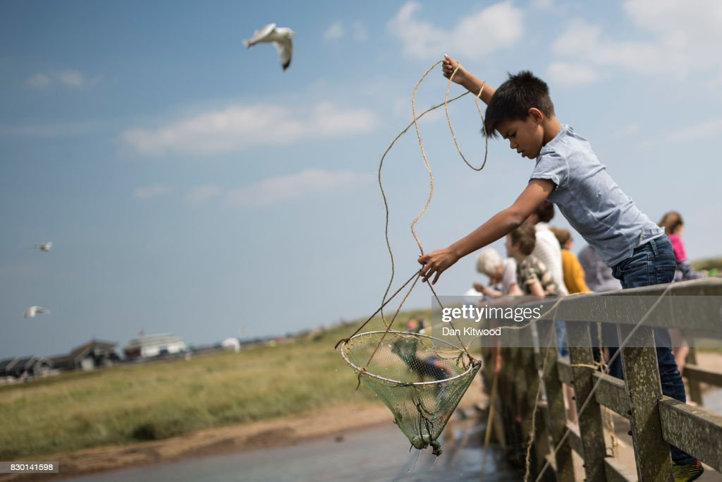 A young boy fishes for crabs from a wooden bridge on August 11, 2017 in Walberswick, England. Much of the country is expected to enjoy a sunny spell over the weekend after a period of unseasonably wet weather.