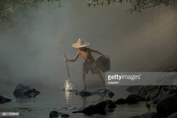 Young boy fishing with a spear, Nong Khai, Thailand