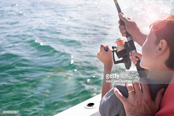 young boy fishing with dad's help