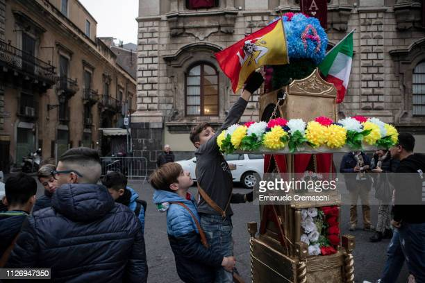 A young boy fixes a flag of Sicily on the top of a miniature of a so called 'candelora' during the celebrations of the 'Festa di Sant'Agata' the...