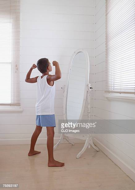 young boy flexing his biceps in front of a mirror - in front of stock pictures, royalty-free photos & images