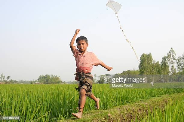 A young boy flies kite in paddy field Bangladesh 2007