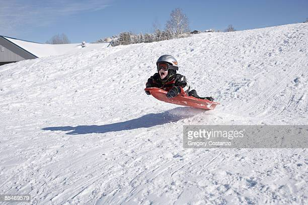 Young Boy Flies of a Jump on a Sled