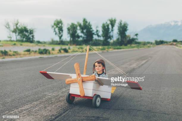 young boy flies toy airplane - aviation hat stock photos and pictures