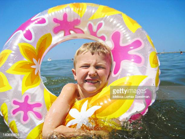 Young boy floating in tube at lake