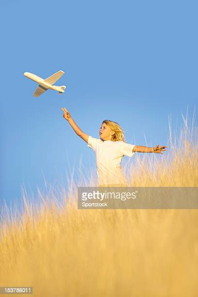 Young Boy Flying Toy Glider Airplane in Field
