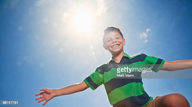 young boy flying with arms out against a blue sky. - captiva island - fotografias e filmes do acervo