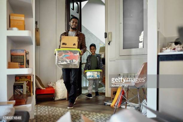 young boy following father into new apartment on moving day - entering stock pictures, royalty-free photos & images